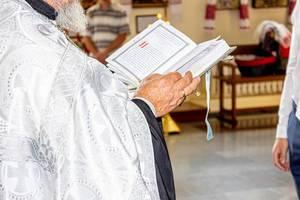 Priester / Pfarrer hält eine Bibel in den Händen