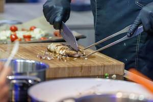 Professional chef chopping grilled meat on a cutting board
