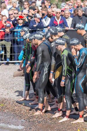 Professional male athletes at the starting line of the Ironman Triathlon in Lahti, ready for the first discipline swimming