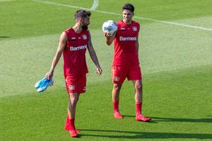 Professional soccer player Nadiem Amiri holding up a Derbster soccer ball, while talking to team member Kerem Demirbay