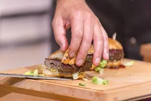 Profi-Koch schneidet einen Hamburger