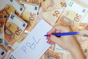 Profit and Loss Statement: Frau schreibt P&L 50 auf einen Zettel zwischen 50-Euro-Noten