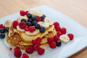 Protein Pancakes with berries, bananas and honey on a white plate