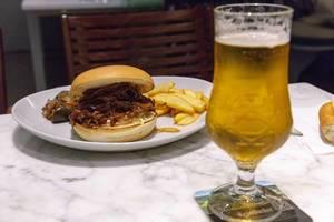 Pulled Beef Burger mit Pommes und Gemüse auf einem weißen Teller mit einem Glas Bier