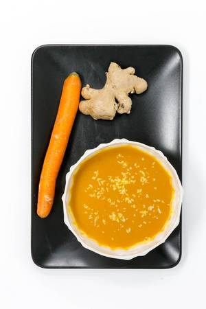 Pumpkin Coconutsoup with Ginger in a bowl placed on a black plate with a carrot and a ginger root