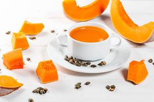Pumpkin orange soup with slices of fresh pumpkin and seeds on white wooden background