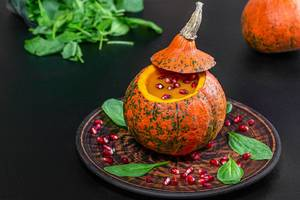 Pumpkin puree and pomegranate in fresh pumpkin with spinach leaves on black background