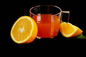 Punsch im Glas, mit frischen Orangen, vor schwarzem Hintergrund