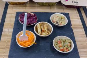 PUR - veganer Bio Nudelsalat, Quinoasalat und Rote Betesalat als Proben in Schälchen auf einer Messer