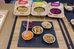 PUR - veganer Bio Nudelsalat, Quinoasalat und Rote Betesalat als Proben in Schälchen mit Verpackungen auf einer Messer
