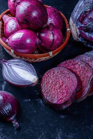 Purple onion, cabbage and beet on black background