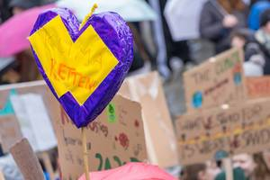 """Purple-yellow heart with """"Save the climate!"""" text and other signs in the background"""