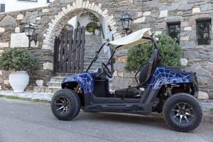 Quad-Leihfahrzeug vor der Steinmauer des Hotels Antirides, auf der Mittelmeerinsel Paros, Griechenland