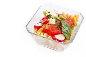 Quadratische Schale mit Nudelsalat verfeinert mit Tomate, Rucola, Radieschen und Fetakäse