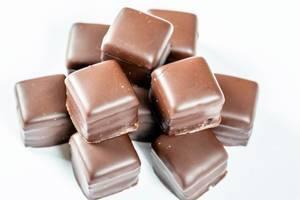 Quadratische Süßigkeiten mit Lebkuchen und Schokoladenüberzug vor weißem Hintergrund