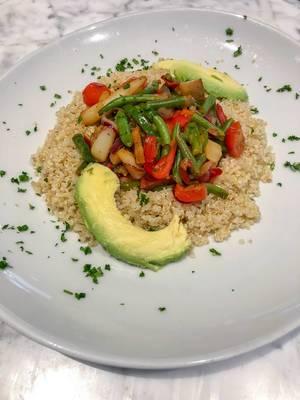 Quinoa mit blanchiertem Gemüse und Avocado auf einem weißen Teller mit Petersilie garniert
