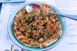 Quinoa-Tamboule mit frischen Tomaten aus Paros, Zwiebeln, Petersilie und Olivenöl auf Fladenbrot