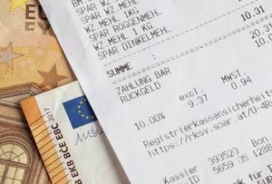 Quittung über Einkauf im Supermarkt liegt auf Euro-Banknoten