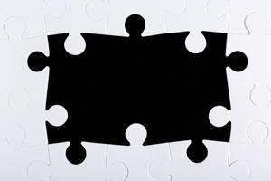 Rahmen aus weißen Puzzleteilen vor schwarzem Hintergrund mit leerem Raum in der Mitte