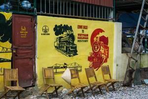 Railway Cafe in Hanoi - nahe der Bahnschienen stehen vier Stühle