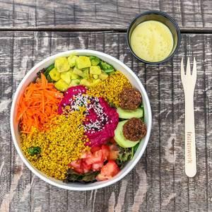 Rainbow Bowl: bunter Spinat-Mix, Avocadowürfel, Pink Hummus, Falafelbällchen, Gurkenscheiben, Quinoa, Karottenstreifen, Tomatenwürfel, Sauce