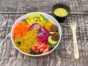Rainbow Bowl: colorful spinach mix, avocado cubes, pink hummus, falafel, cucumber slices, quinoa, carrot stripes, tomato cubes, dressing