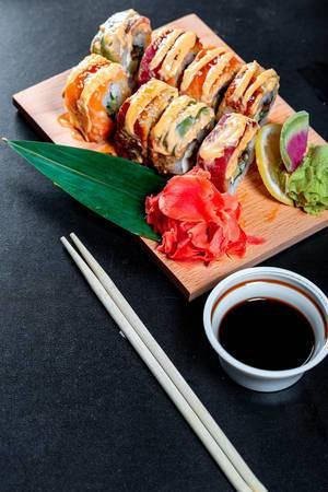 Rainbpw Dragon Sushi mit Sojasoße und Essstäbchen auf schwarzem Hintergrund