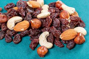 Raisins and different nuts on a green background (Flip 2019)