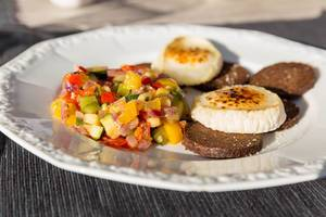 Ratatouille, Pumpernickel und flambierter Käse auf einem weißen Teller