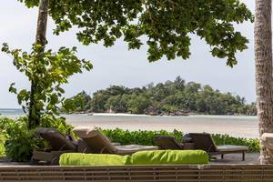 Rattan furniture under tropical trees on Mahé, Seychelles infant of tiny island in the Indian Ocean