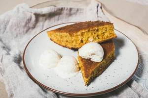 Rautenförmige Stücke vom Möhrenkuchen mit Vanilleeis auf einem Teller und Leinentuch