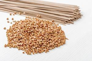 Raw buckwheat and buckwheat soba noodles on white wooden background (Flip 2019)