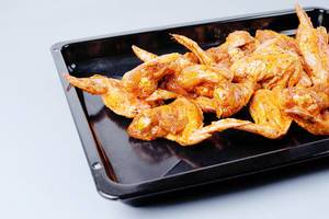 Raw chicken wings in pan, white background (Flip 2019)