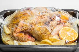 Raw chicken with spices, potatoes and oranges in a baking tray before baking