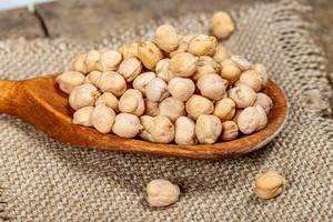 Raw chickpeas grain in a wooden spoon on burlap (Flip 2019)