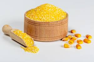 Raw corn grits in a wooden bowl and scoop on a white background