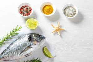 Raw fresh Dorada on a white wooden table with spices, rosemary, lime slices and starfish