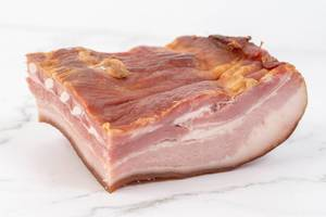 Raw homemade pork bacon on the white marble board