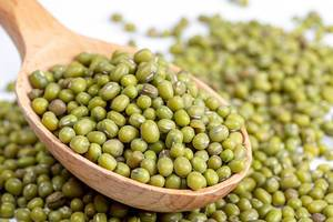 Raw mung beans in wooden spoon