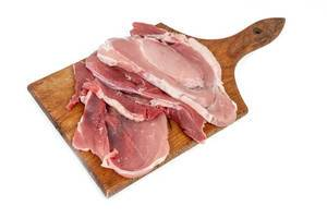 Raw Pork Chops on the wooden cutting board