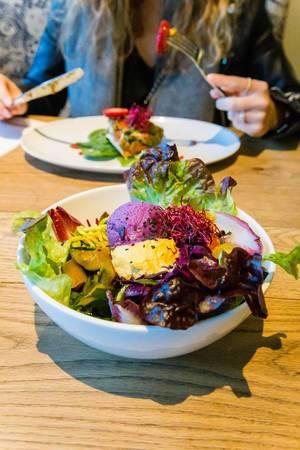 Raw Superbowl mit bunter Rohkost, Rotkohlhummus und Orangenhummus auf Krautsalat im Flex&Kale Restaurant in Barcelona