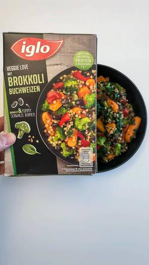 Ready-made vegan meal by Iglo: Veggie love with broccoli and buckwheat served in a black bowl on white background