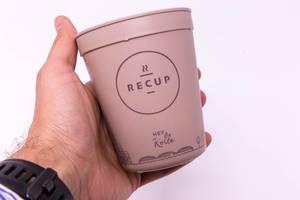 RECUP Kaffebecher - Hey Kölle in einer Hand gehalten