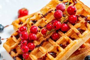 Red currant on waffles with chocolate topping close-up (Flip 2019)