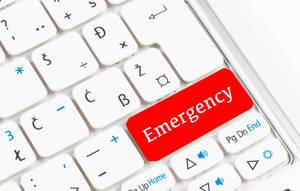 Red emergency button on white keyboard