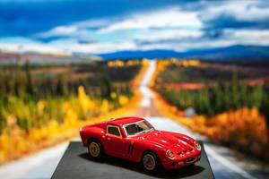 Red Ferrari toy car on platform with scenery background (Flip 2019)