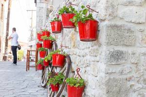 Red flowerpots mounted on hooks on a house wall
