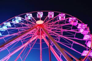 Red lighted Ferris wheel, night view