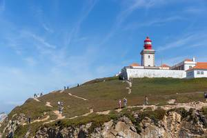 Red Lighthouse with Tourists at the Cabo da Roca coast in Portugal