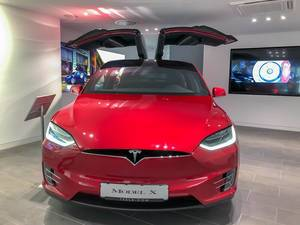 Red Tesla Model X with wing doors
